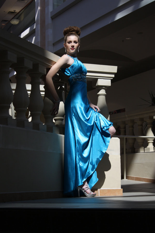 Model Addison wears a turquoise satin gown with jewel embellishments, $139.99. Silver crystal-infused sandal from Deb Shops, $40.50. All sold at Deb Shops. Photo by Steve Webb for The Oklahoman.