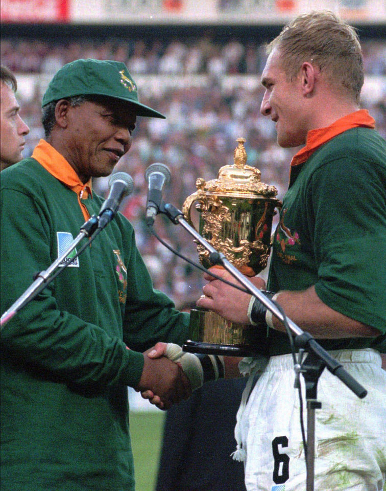 FILE - In this June 24, 1995 file photo, South African rugby captain Francios Pienaar, right, receives the Rugby World Cup trophy from President Nelson Mandela, left, who wears a South African rugby shirt, after South Africa defeated New Zealand in the finals in Johannesburg.   South Africa's president Jacob Zuma says, Thursday, Dec. 5, 2013, that Mandela has died. He was 95.  (AP Photo/Ross Setford, File)