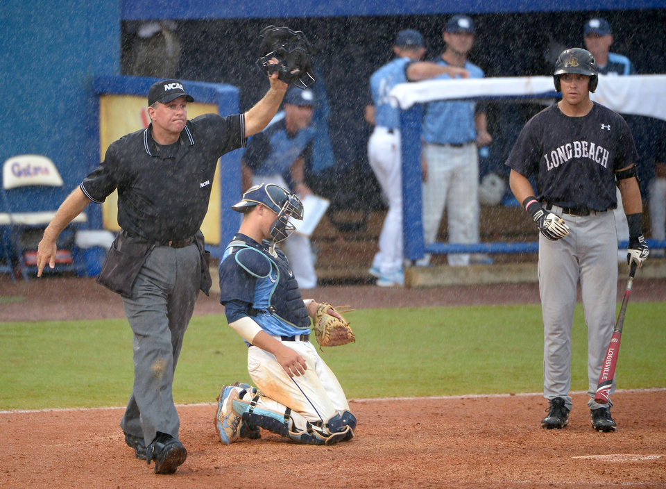 Photo - Home plate umpire Don Goller, left, halts play for a second time as rain falls during the seventh inning of an NCAA college baseball regional tournament game as North Carolina catcher Korey Dunbar, center, and Long Beach State's Richard Prigatano watch in Gainesville, Fla., Sunday, June 1, 2014.(AP Photo/Phelan M. Ebenhack)