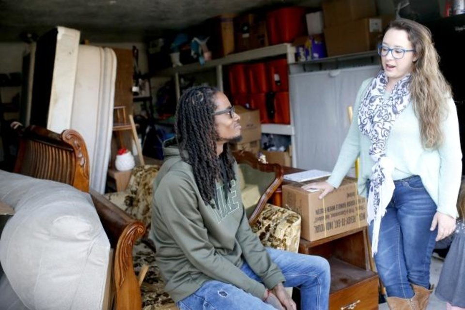 Photo -  Lynda Steele, founder of Furnishing Fatherhood, right, talks with one of the dads who has benefited from the organization, Allen Shaw, as the two meet in her garage filled with donated items. [Sarah Phipps/The Oklahoman]