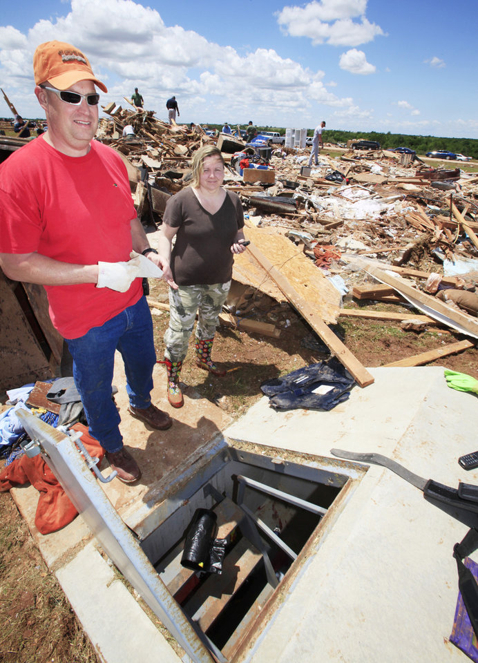 Photo - Tornado aftermath cleanup east of Piedmont, Wednesday, May 25, 2011.     Chad and Becky Brown with their storm shelter that they shared with 13 people during Tuesdays tornado.   Photo by David McDaniel, The Oklahoman