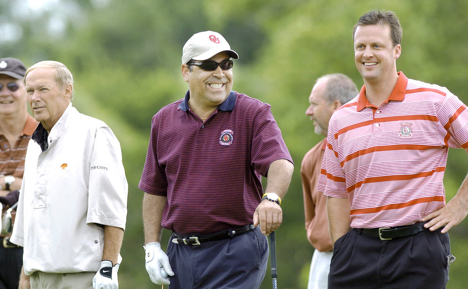 Photo - OU basketball coach Kelvin Sampson laughs while waiting to hit a tee shot. At left is former basketball coach Billy Tubbs.  At right is Cale Gundy, a former OU quarterback and now an assistant football coach at OU.      Staff photo by Jim Beckel.