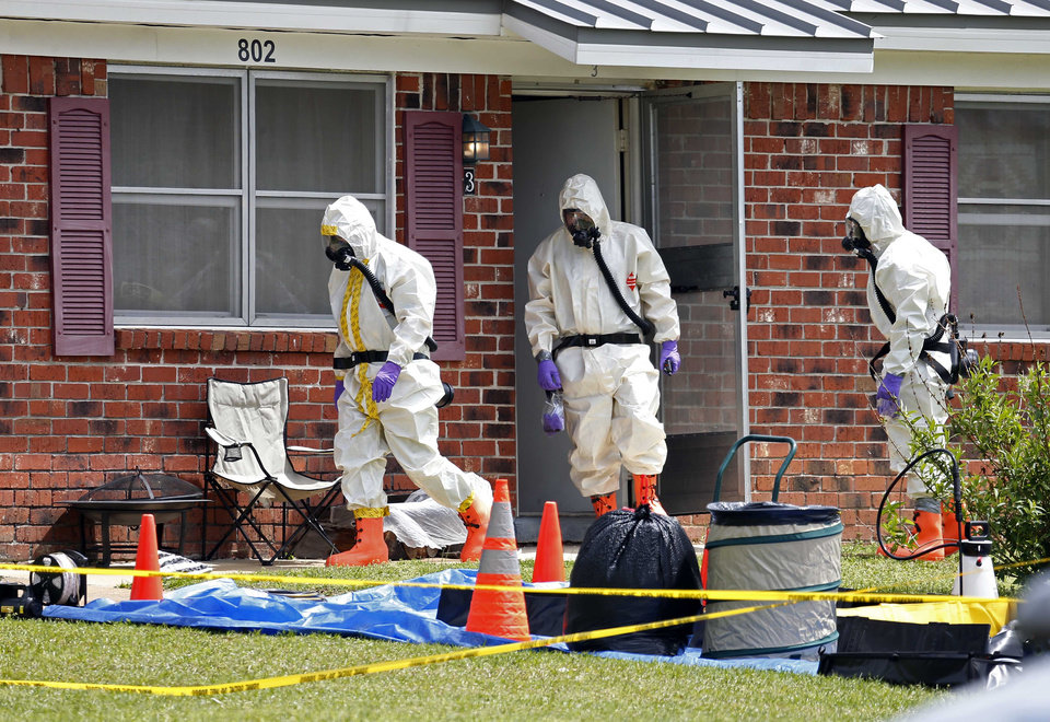 Photo - Federal agents wearing hazardous material suits and breathing apparatus exit the home and possessions in the West Hills Subdivision house of Paul Kevin Curtis in Corinth, Miss., Friday, April 19, 2013. Curtis is in custody under the suspicion of sending letters covered in ricin to the U.S. President Barack Obama and U.S. Sen. Roger Wicker, R-Miss. (AP Photo/Rogelio V. Solis)