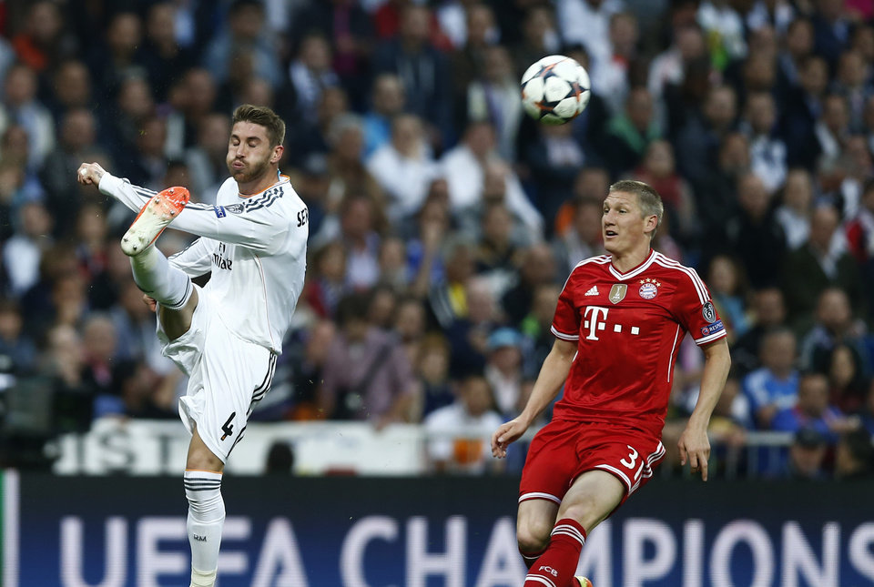 Photo - Real's Sergio Ramos kicks the ball next to Bayern's Bastian Schweinsteiger, right, during a first leg semifinal Champions League soccer match between Real Madrid and Bayern Munich at the Santiago Bernabeu stadium in Madrid, Spain, Wednesday, April 23, 2014. (AP Photo/Andres Kudacki)