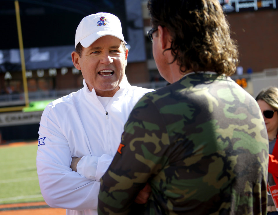 Photo - Kansas head football coach Les Miles and Oklahoma State University head football coach Mike Gundy talk before the college football game between the Oklahoma State University Cowboys and the Kansas Jayhawks at Boone Pickens Stadium in Stillwater, Okla., Saturday, Nov. 16, 2019.  [Sarah Phipps/The Oklahoman]