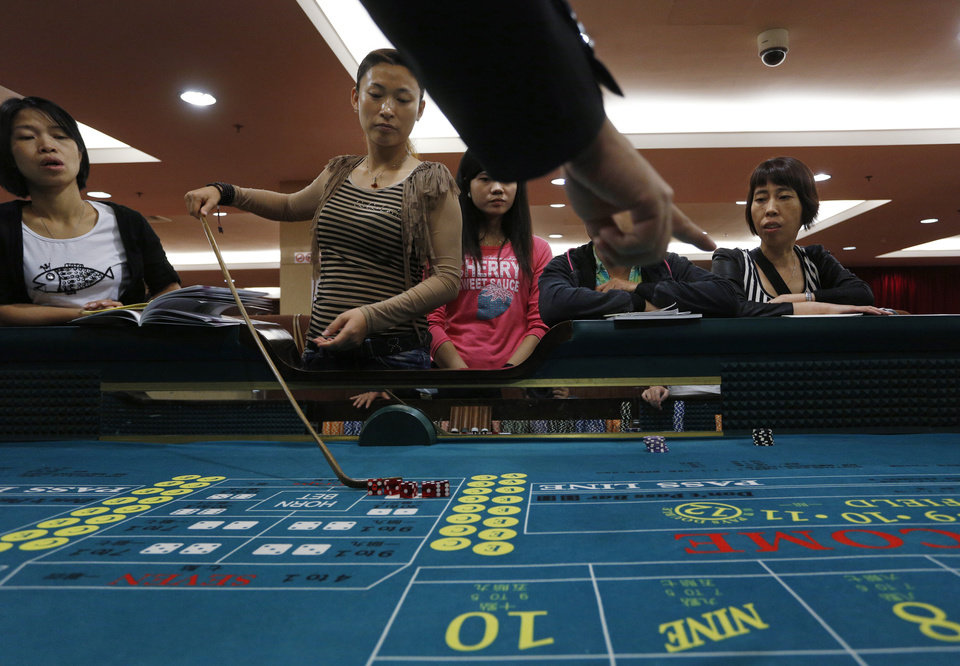 In this Oct. 25, 2012 photo, a gambling school students take a practice on a tabel in Macau, China. Hordes of Chinese high rollers flooding into Macau have turned the city into an Asian casino boomtown but they�re also posing a challenge for China�s next generation of leaders.(AP Photo/Vincent Yu)