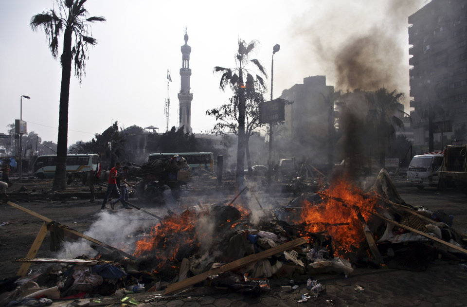 Photo - The remains of tents burn outside Rabaah al-Adawiya mosque, where supporters of Egypt's ousted President Mohammed Morsi had a protest camp at Nasr City, Cairo, Egypt, Thursday, Aug. 15, 2013. Egypt faced a new phase of uncertainty on Thursday after the bloodiest day since its Arab Spring began, with hundreds of people reported killed and thousands injured as police smashed two protest camps of supporters of the deposed Islamist president. Wednesday's raids touched off day-long street violence that prompted the military-backed interim leaders to impose a state of emergency and curfew, and drew widespread condemnation from the Muslim world and the West, including the United States. (AP Photo/Khalil Hamra)