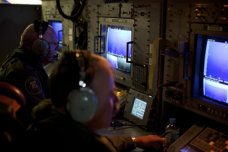 Photo - In this Monday, March 24, 2014 photo, crewmen on board an RAAF AP-3C Orion aircraft look at their radar screens whilst searching for missing Malaysia Airlines Flight MH370 over the Indian Ocean. After 17 days of desperation and doubt over the missing Malaysia Airlines jet, Malaysian officials on Monday said an analysis of satellite data points to a