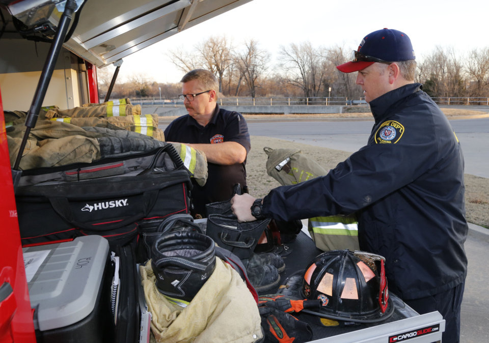 Photo -  Oklahoma City fire investigators Steve Strother and Brian Cosner organize equipment in their fire investigation truck. [Photo by Paul Hellstern, The Oklahoman]
