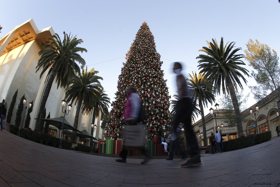 In this Thursday, Dec. 20, 2012, photo,  holiday shoppers walk past a large Christmas tree at Fashion Island shopping center in Newport Beach, Calif. U.S. consumers increased their spending at retail businesses in December, buying more autos, furniture and clothing. (AP Photo/Chris Carlson)