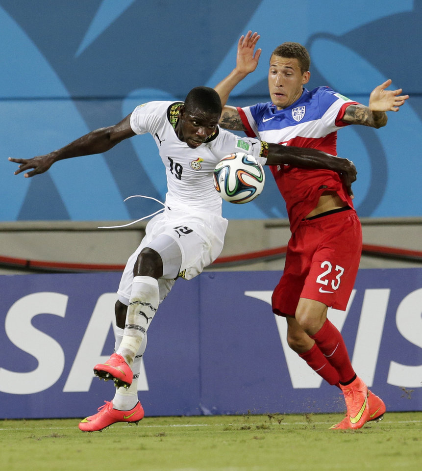 Photo - Ghana's Jonathan Mensah, left, pushes off United States' Fabian Johnson during the group G World Cup soccer match between Ghana and the United States at the Arena das Dunas in Natal, Brazil, Monday, June 16, 2014.  (AP Photo/Petr David Josek)