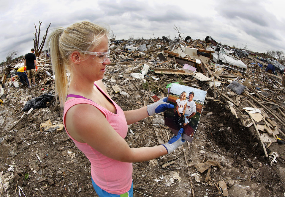 "Jill Tompkins, 28, stands in the rubble of her home at 1001 SW 15, holding a picture of her with her dad, Larry Tompkins, when she was a young softball player for the Washington Wild Things. A volunteer from Moore First Baptist Church had just handed her these photos after he recovered them from the debris. Tompkins thanked him repeatedly and smiled big, explaining to him why these pictures are of such value to her. Her dad, who was her softball coach from age five through high school, died in March. She said her dad ""had me out there practicing every day."" She didn't like it too much then, but now says she is very thankful. While at Washington High School, her teams won four state softball championships. She found three of her four state rings in the storm's aftermath. She said she is amazed she escaped unhurt and is ""so thankful"" to have survived the strong tornado.  Volunteers from various parts of the country joined Oklahomans in assisting residents on Saturday,  May 25, 2013, doing whatever was needed to remove debris and salvage items from this neighborhood east of Santa Fe, north of SW 19 Street.  An EF5 tornado leveled many neighborhoods in Moore and southwest Oklahoma City last Monday.   Photo  by Jim Beckel, The Oklahoman."