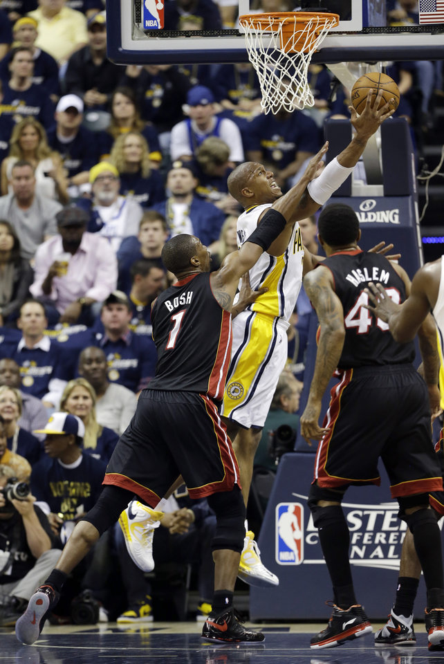 Photo - Indiana Pacers' David West (21) puts up a shot against Miami Heat's Chris Bosh (1) and Udonis Haslem (40) during the first half of Game 3 of the NBA Eastern Conference basketball finals in Indianapolis, Sunday, May 26, 2013. (AP Photo/Nam H. Huh)