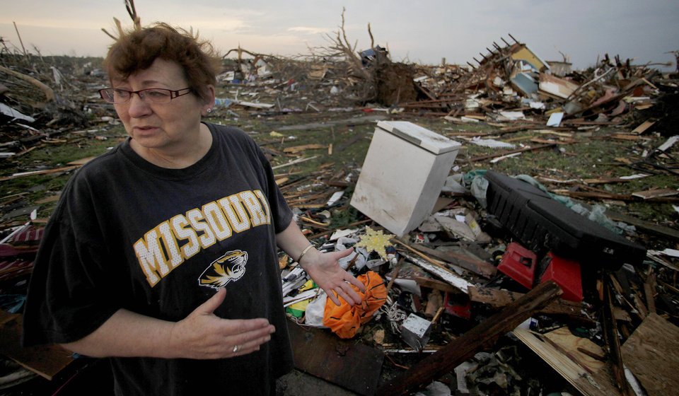 Photo - Anita Stokes surveys her home that was destroyed by a tornado in Joplin, Mo., Monday, May 23, 2011. A large tornado moved through much of the city Sunday, damaging a hospital and hundreds of homes and businesses and killing at least 89 people. (AP Photo/Charlie Riedel) ORG XMIT: MOCR212