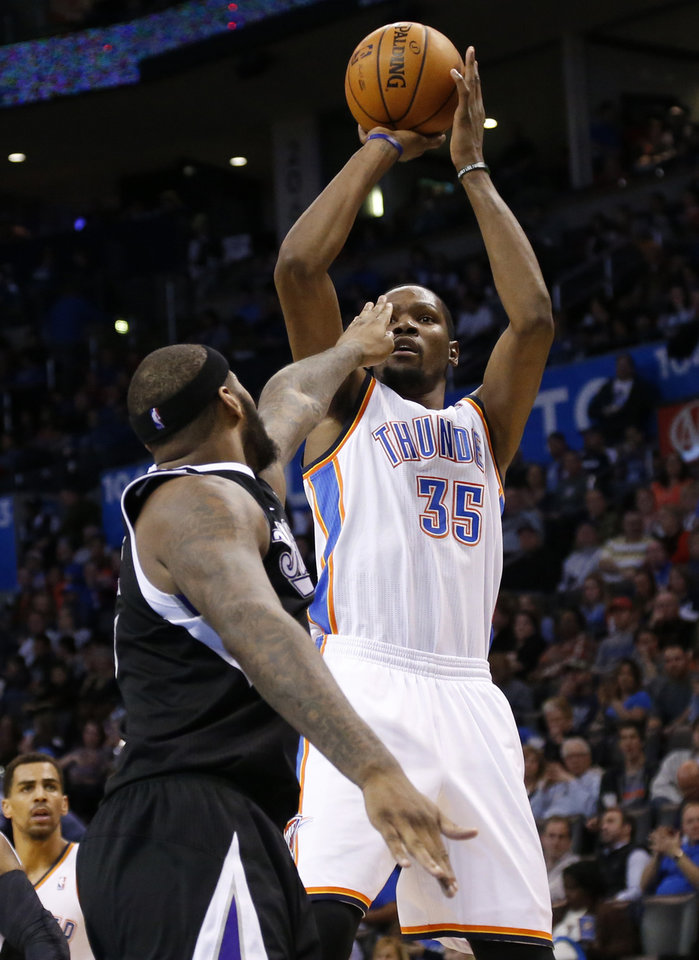 Photo - Oklahoma City Thunder forward Kevin Durant (35) shoots as Sacramento Kings center DeMarcus Cousins (15) defends in the third quarter of an NBA basketball game in Oklahoma City, Sunday, Jan. 19, 2014. Oklahoma City won 108-93. (AP Photo/Sue Ogrocki)