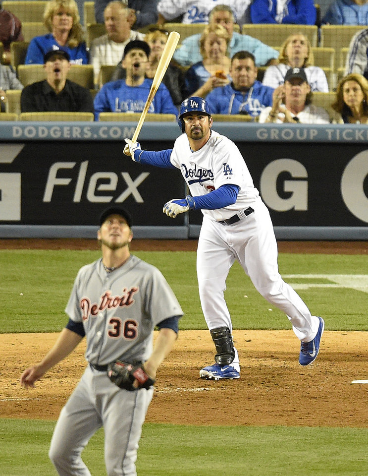 Photo - Los Angeles Dodgers' Adrian Gonzalez, right, hits a solo home run as Detroit Tigers relief pitcher Joe Nathan looks on during the ninth inning of a baseball game, Wednesday, April 9, 2014, in Los Angeles. (AP Photo/Mark J. Terrill)