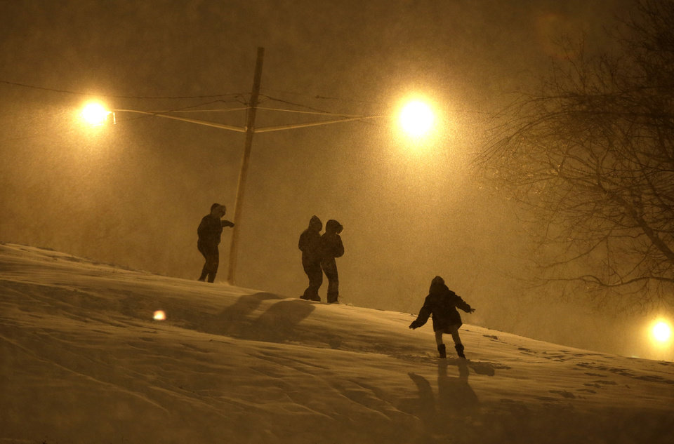 Photo - People walk on the snow covered hill of Leonard Gordon Park as snow falls over them, Thursday, Jan. 2, 2014, in Jersey City, N.J. Snow and bone-chilling temperatures are expected for the overnight hours with substantial accumulation predicted. (AP Photo/Julio Cortez)