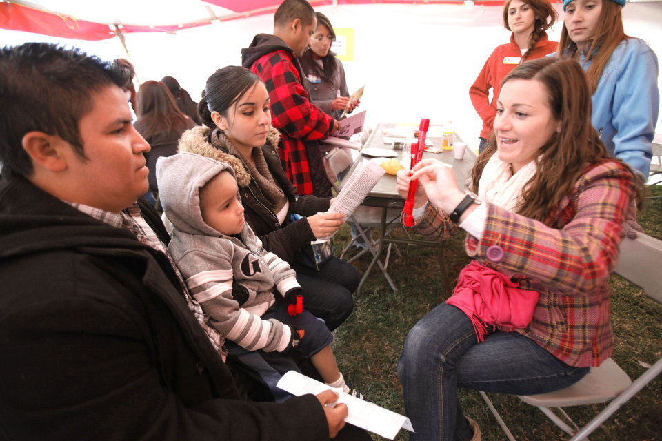 UCO Dietetic intern Megan Shamleffer talks about cholesterol with Javier Ortega, Christopher Ortega, 3, and Sarai Ortega as LOVE OKC and Convoy of Hope distributed goods and services Saturday to metro residents at the old John Marshall High School in Oklahoma City.  Photo By Paul Hellstern, The Oklahoman