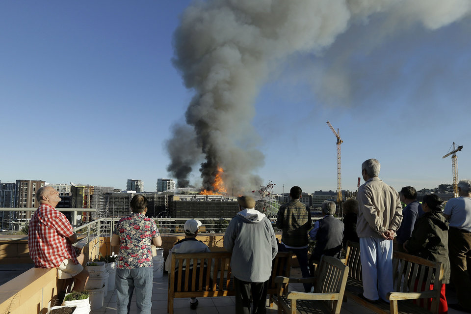 Photo - Residents at Mission Creek Senior Community building look from their roof at a fire burning in San Francisco, Tuesday, March 11, 2014. The major fire burning in San Francisco's Mission Bay neighborhood sent an enormous plume of black smoke high into the sky. There were no initial reports of injuries. The four-alarm fire that began about 5 p.m. was ravaging a high-rise building under construction and moving down a block. Fire-suppression systems had not yet been installed in the building, making the battle against the blaze more difficult, Fire Department spokeswoman Mindy Talmadge said. (AP Photo/Jeff Chiu)