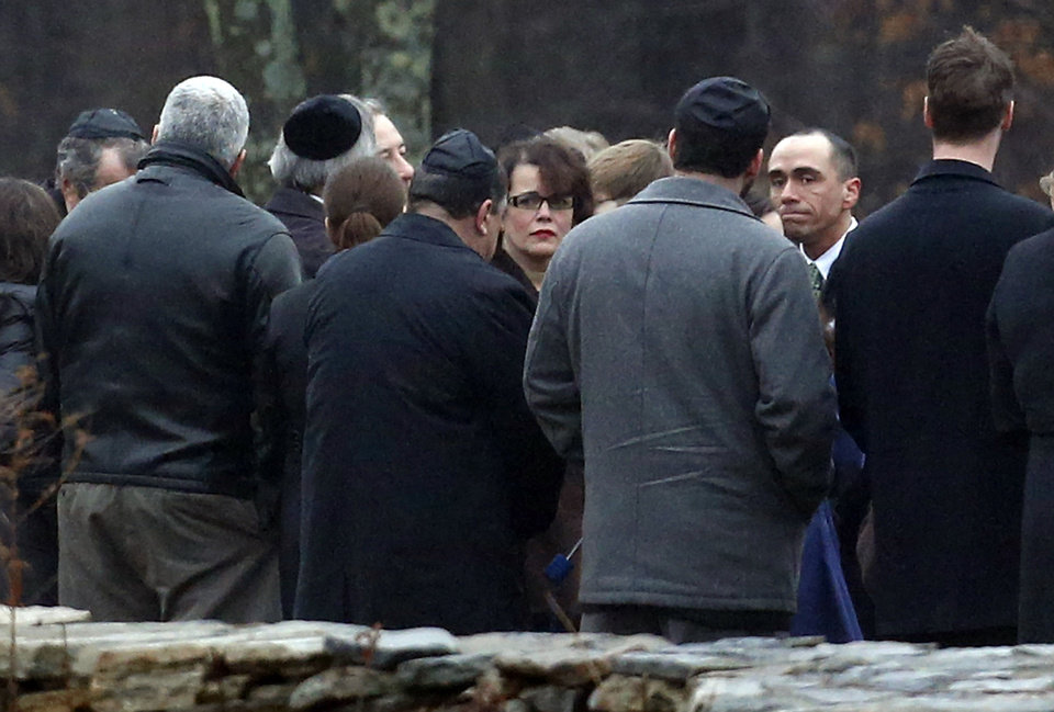 Photo - Veronique Pozner, center, walks near people at B'nai Israel Cemetery during burial services for her 6-year-old son Noah Pozner, Monday, Dec. 17, 2012, in Monroe, Conn. Noah Pozner was killed when Adam Lanza walked into Sandy Hook Elementary School in Newtown, Conn., Friday and opened fire, killing 26 people, including 20 children, before killing himself. (AP Photo/Julio Cortez) ORG XMIT: CTJC130