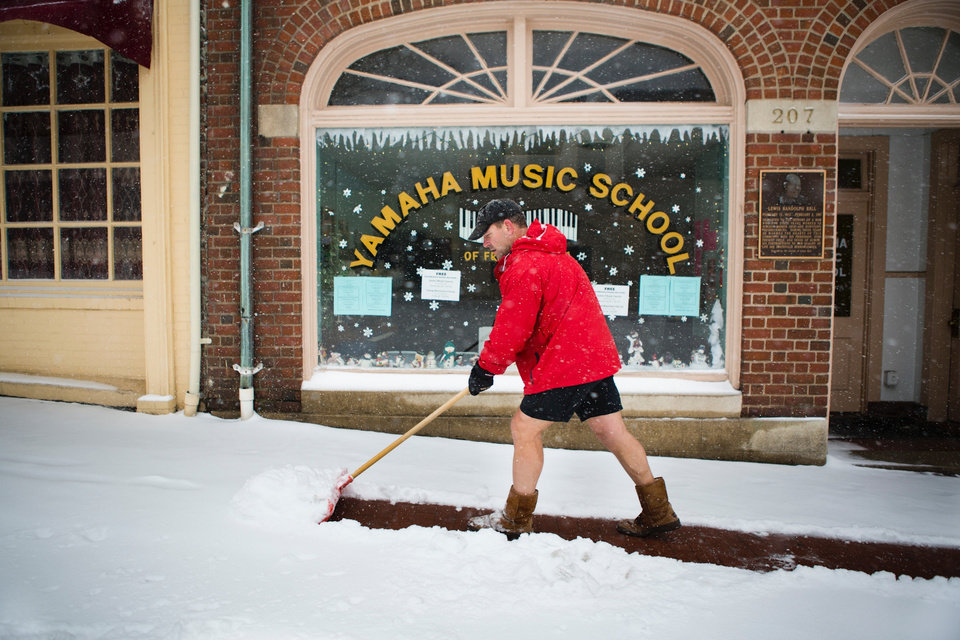 Photo - Owner of Bodywork Wayne Gootee shovels the walkway in front of businesses in Fredericksburg, Va during the snowstorm on Monday, March 3, 2014. Winter kept its icy hold on much of the country Monday, with snow falling and temperatures dropping as schools and offices closed and people from the South and Mid-Atlantic to Northeast reluctantly waited out another storm indoors. (AP Photo/The Free Lance-Star,  Autumn Parry)