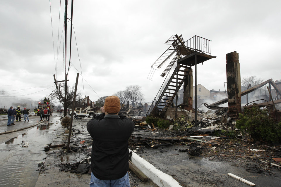 A man photographs damage caused by a fire fire in the Belle Harbor neighborhood in the New York City borough of Queens Tuesday, Oct. 30, 2012, in New York. Sandy, the storm that made landfall Monday, caused multiple fatalities, halted mass transit and cut power to more than 6 million homes and businesses. (AP Photo/Frank Franklin II) ORG XMIT: NYFF142