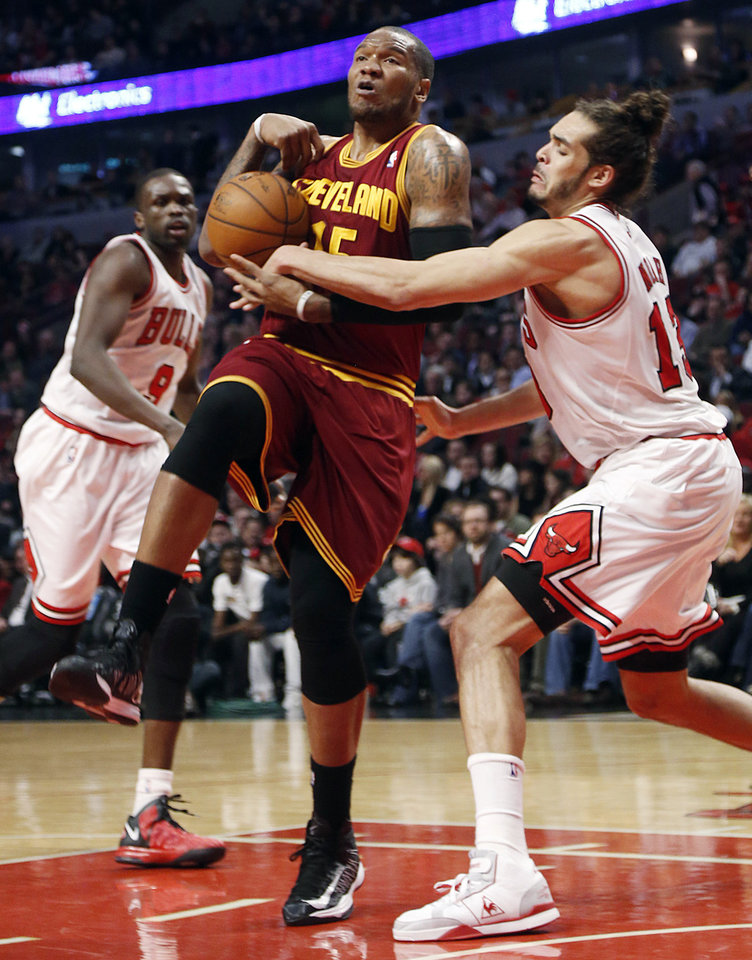 Photo - Chicago Bulls' Joakim Noah (13) slaps ball from the hands of Cleveland Cavaliers' Marreese Speights during the second quarter of an NBA basketball game, Tuesday, Feb. 26, 2013, in Chicago.(AP Photo/Charles Cherney)