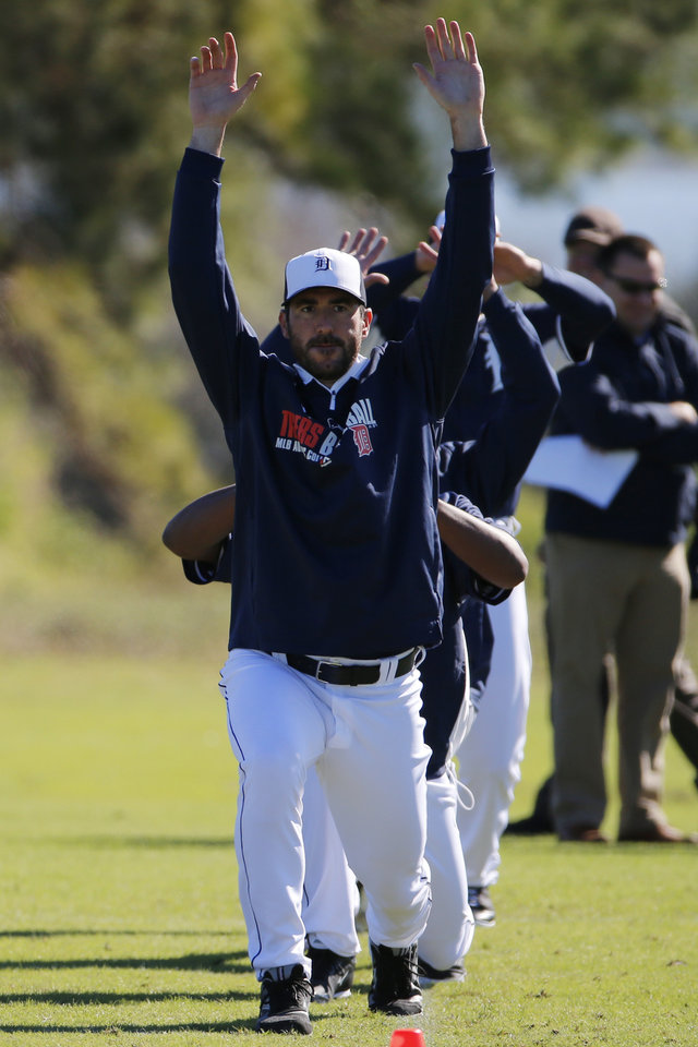 Photo - Detroit Tigers pitcher Justin Verlander leads a group through warmups on the team's first day of baseball spring training for pitchers and catchers in Lakeland, Fla., Friday, Feb. 14, 2014. (AP Photo/Gene J. Puskar)