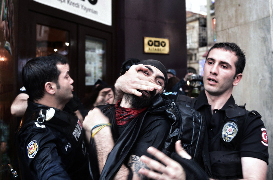 Photo - Riot police detain a protester as they use water cannons and teargas to disperse people who were protesting the Soma mine accident that killed 301 miners, in Istanbul, Turkey, Saturday, May 17, 2014. Turkey's Energy Minister Taner Yildiz said Saturday that crews had found more bodies overnight, raising the death toll to 301. An explosion and fire at a coal mine in Soma, some 250 kilometers (155 miles) south of Istanbul, killed hundreds of workers in one of the worst mining disasters in Turkish history. (AP Photo
