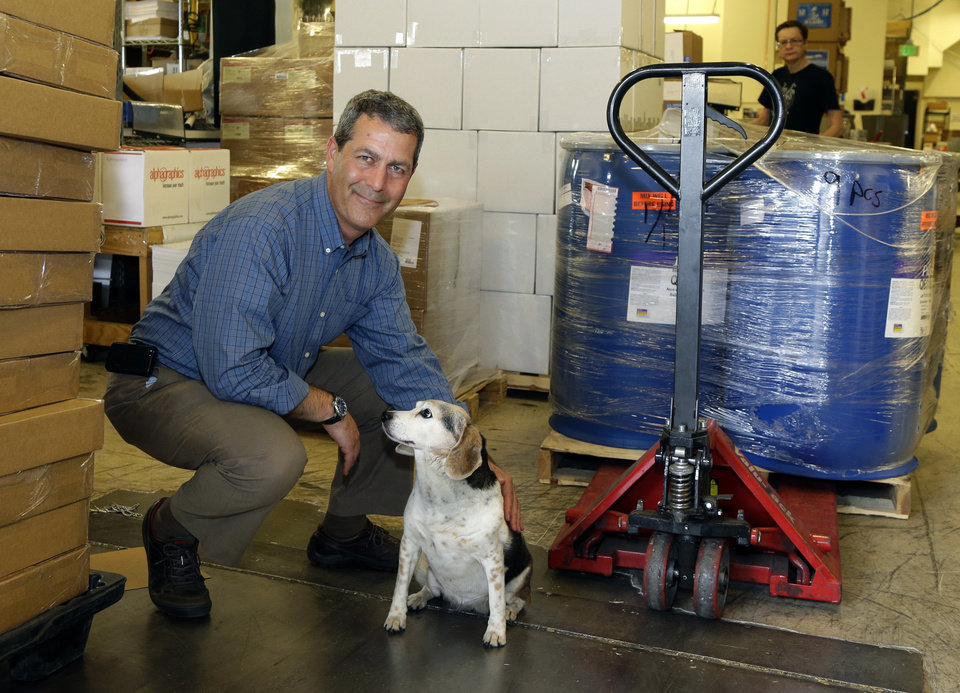 Photo - In this Monday, June 23, 2014 photo, Chuck Stempler, owner of an AlphaGraphics printing and marketing franchise, poses for a photo with his dog, Dagny, in the shipping and receiving area of his business, in Seattle. Stempler, who is a plaintiff in a federal lawsuit seeking to overturn a Seattle law that will raise the city's minimum wage to $15 from the current $9.32, says he will have to cut jobs to afford the higher wage. (AP Photo/Ted S. Warren)