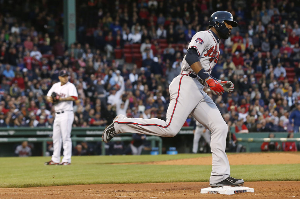 Photo - Atlanta Braves' Jason Heyward, right, rounds the bases after his solo home run off of Boston Red Sox starting pitcher Jake Peavy, left, during the third inning of a baseball game at Fenway Park, Thursday, May 29, 2014, in Boston. (AP Photo/Winslow Townson)