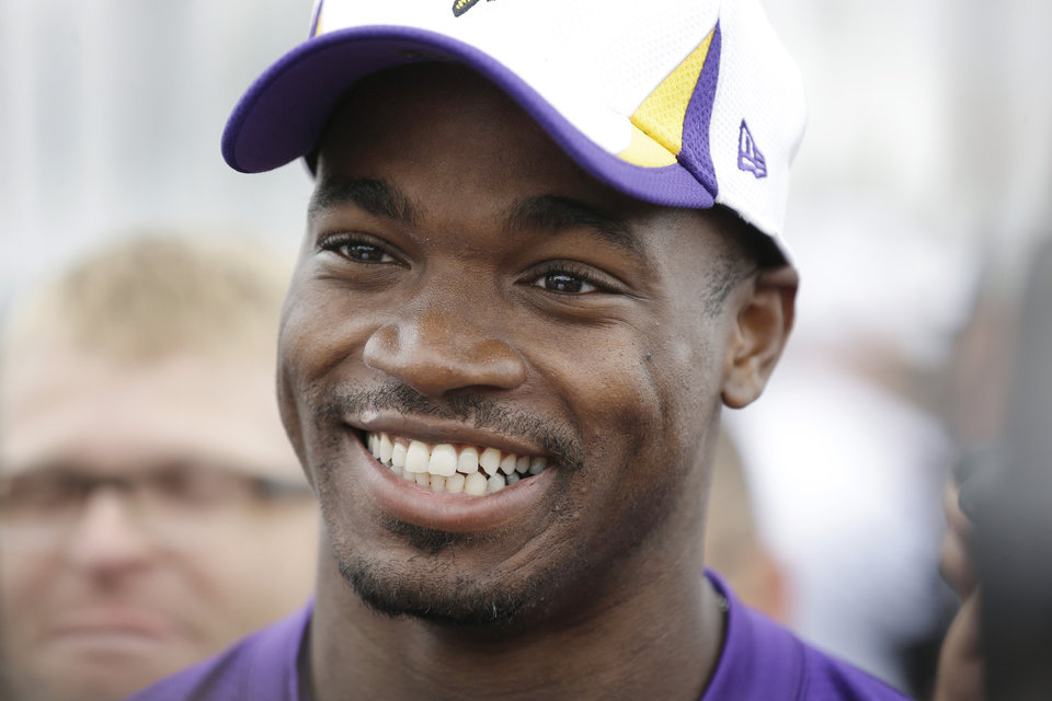Photo - Minnesota Vikings running back Adrian Peterson speaks to the media following practice at NFL football training camp, Friday, July 26, 2013, in Mankato, Minn. (AP Photo/Charlie Neibergall)
