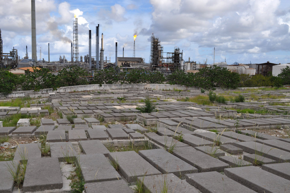 In this Nov. 12, 2012 photo, tombs in the Beth Haim cemetery are back dropped by the Isla oil refinery in Blenheim, on the outskirts of Willemstad, Curacao. Beth Haim, believed to be one of the oldest Jewish cemeteries in the Western Hemisphere, established in the 1950s and considered an important landmark on an island where the historic downtown has been designated a UNESCO World Heritage Site, is slowly fading in the Caribbean sun. Headstones are pockmarked with their inscriptions faded, stone slabs that have covered tombs in some cases for hundreds of years are crumbling into the soil, marble that was once white is now grey, likely from the acrid smoke that spews from the oil refinery that looms nearby. (AP Photo/Karen Attiah)