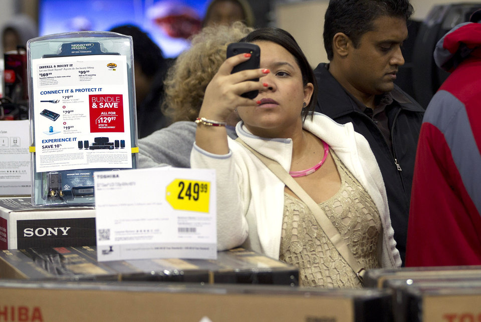 FILE - In this Thursday, Nov. 22, 2012, file photo a shopper uses her smart phone at the Pembroke Pines, Fla. Best Buy. Facebook isn\'t just for goofy pictures and silly chatter. Whether shoppers know it or not, their actions online help dictate what\'s in stores during this holiday season. (AP Photo/J Pat Carter, File)