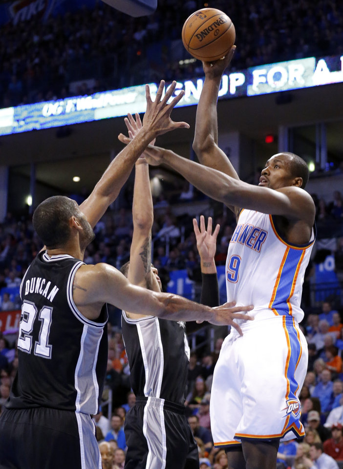 Oklahoma City\'s Serge Ibaka (9) shoots over San Antonio\'s Tim Duncan (21) and Danny Green (4) during the NBA game between the Oklahoma City Thunder and the San Antonio Spurs at the Chesapeake Energy Arena, Thursday, April 4, 2013. Photo by Sarah Phipps, The Oklahoman