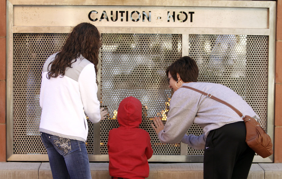 Sierra Witte, left, Zander Gilsdorf, 4, and his mother Bonnie Gilsdorf  warm their hands with an outdoor fireplace at The Outlet Shoppes in Oklahoma City, Friday  November 23, 2012. Photo By Steve Gooch, The Oklahoman