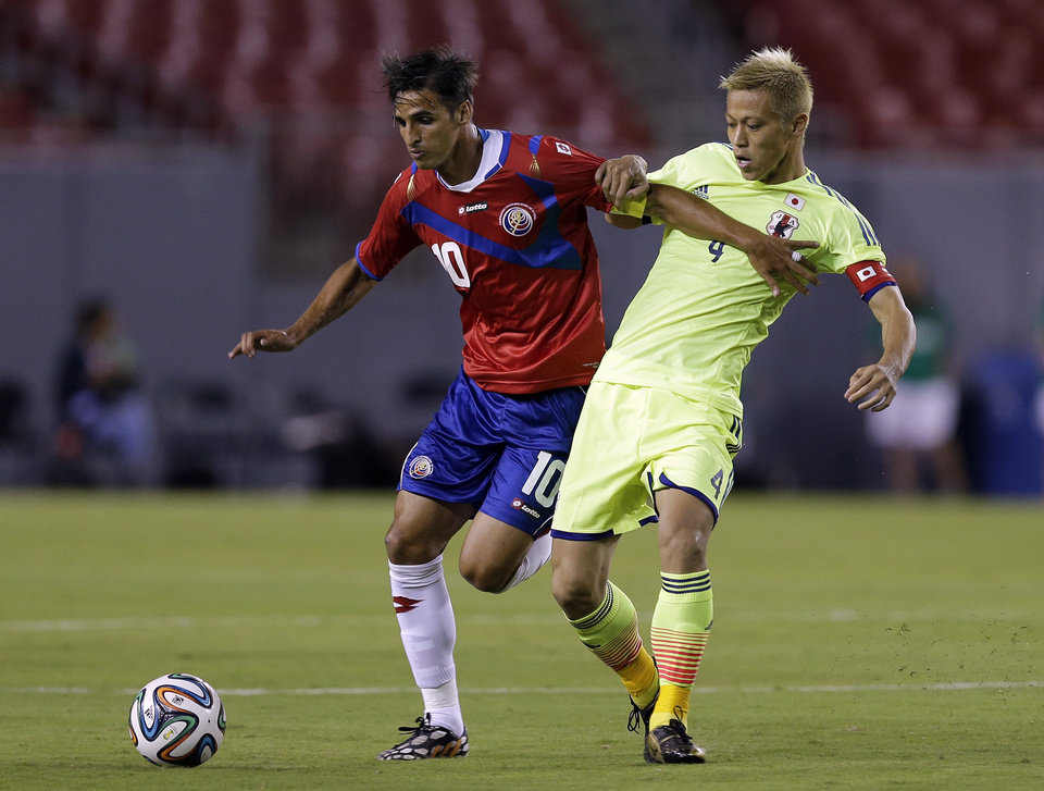 Photo - Costa Rica forward Bryan Ruiz (19) battles with Japan forward Keisuke Honda (4) for the ball during the first half of a friendly soccer match Monday, June 2, 2014, in Tampa, Fla. (AP Photo/Chris O'Meara)