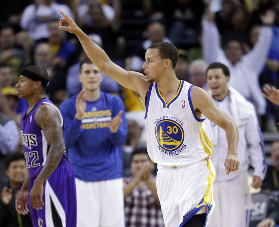 Photo - Golden State Warriors' Stephen Curry (30) celebrates after making a 2-point basket, next to Sacramento Kings' Isaiah Thomas (22) during the first half of an NBA preseason basketball game on Monday, Oct. 7, 2013, in Oakland, Calif. (AP Photo/Marcio Jose Sanchez)