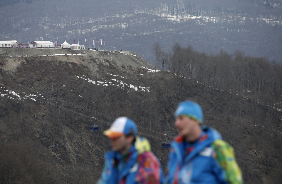 Photo - An inter-mingling of snow and brown patches are seen near the alpine course at the Sochi 2014 Winter Olympics, Tuesday, Feb. 11, 2014, in Krasnaya Polyana, Russia. Warm temperatures in the mountains made the snow too soft and caused the cancellation of Women's downhill training on Tuesday.  (AP Photo/Christophe Ena)