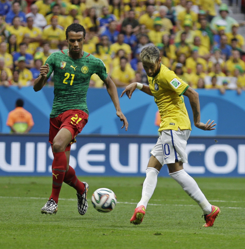 Photo - Brazil's Neymar kicks the ball past Cameroon's Joel Matip to score his side's first goal during the group A World Cup soccer match between Cameroon and Brazil at the Estadio Nacional in Brasilia, Brazil, Monday, June 23, 2014. (AP Photo/Natacha Pisarenko)