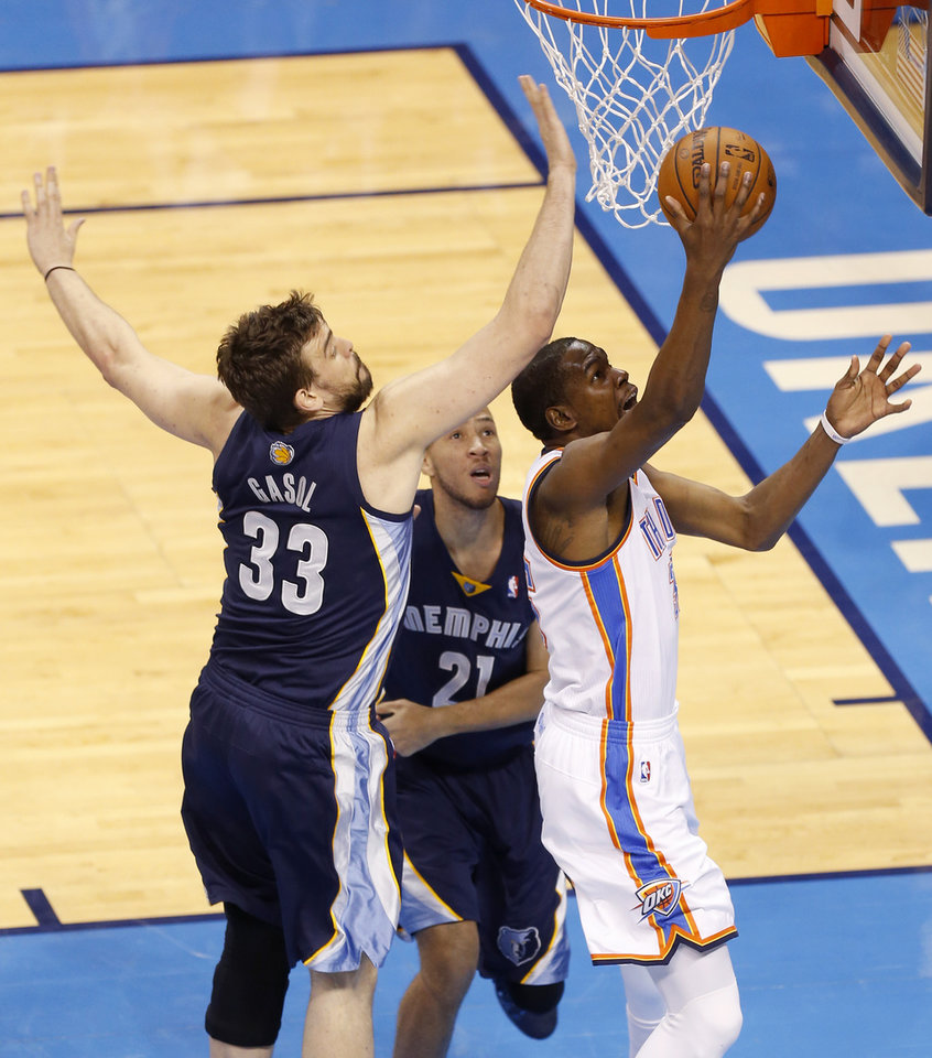 Photo - Oklahoma City's Kevin Durant (35) goes past Memphis' Marc Gasol (33) and Tayshaun Prince (21) during Game 1 in the first round of the NBA playoffs between the Oklahoma City Thunder and the Memphis Grizzlies at Chesapeake Energy Arena in Oklahoma City, Saturday, April 19, 2014. Photo by Nate Billings, The Oklahoman