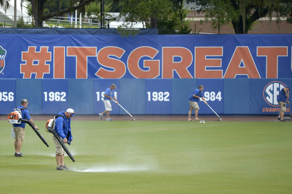Photo - Members of the grounds crew work to remove water from the field during a rain delay in the fourth inning of an NCAA college baseball regional tournament game between Long Beach State and North Carolina in Gainesville, Fla., Sunday, June 1, 2014. (AP Photo/Phelan M. Ebenhack)