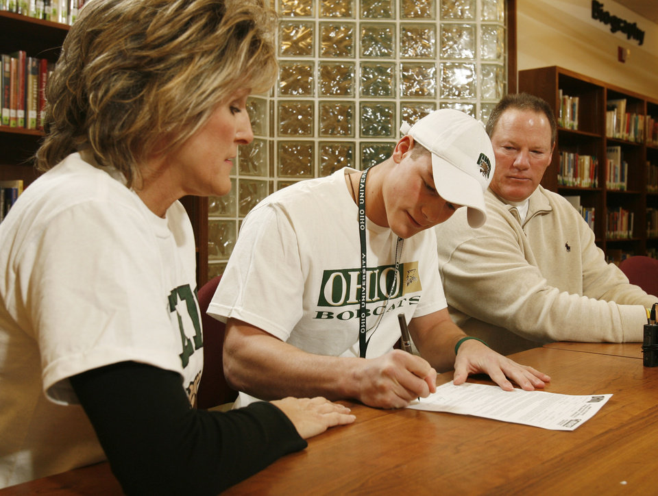 Photo - Tyler Tettleton signs a letter of intent to play college football while his mother Sylvia Nettleton and father Mickey Tettleton watch at Norman North High School in  Norman, Okla. on Wednesday, Feb. 4, 2009.    Photo by Steve Sisney, The Oklahoman