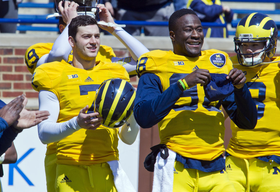 Photo - Michigan quarterback Shane Morris, front left, and quarterback Devin Gardner, front right, laugh as they put on equipment for the football team's annual spring football game on Saturday, April 5, 2014, in Ann Arbor, Mich. (AP Photo/Tony Ding)