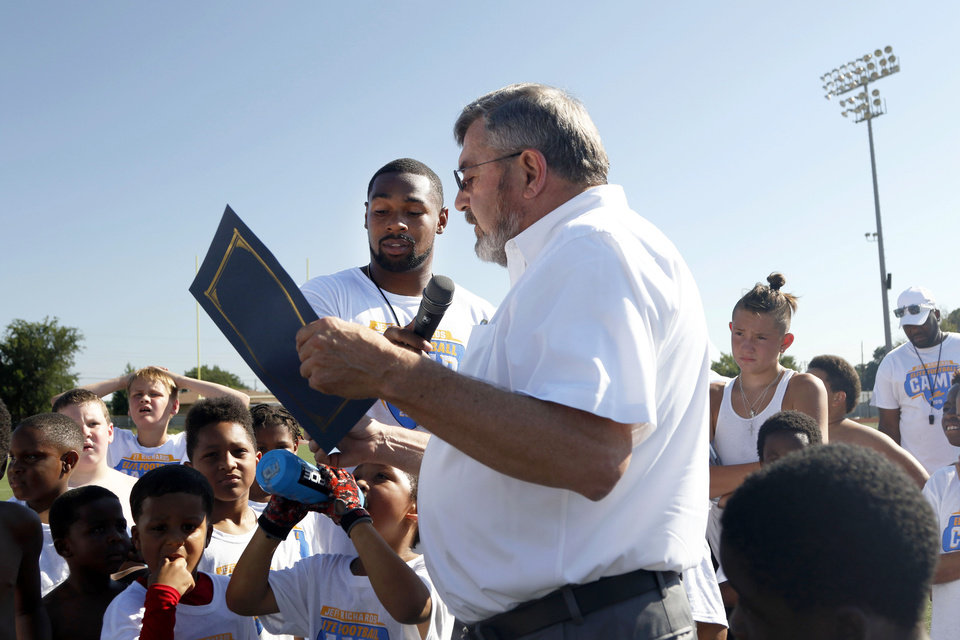 "Photo - Del City mayor Floyd A. Eason reads a declaration stating July 13th as ""Jeff Richards Day"" in Del City at Los Angeles Chargers player Jeff Richards' Elite Football Camp at Del City High School in Del City, Oklahoma on July 13, 2019. [Paxson Haws/The Oklahoman]"