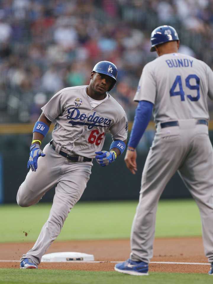 Photo - Los Angeles Dodgers' Yasiel Puig, left, is congratulated by third base coach Lorenzo Bundy while circling the bases after hitting a two-run home run against the Colorado Rockies in the first inning of a baseball game in Denver, Friday, July 4, 2014. (AP Photo/David Zalubowski)