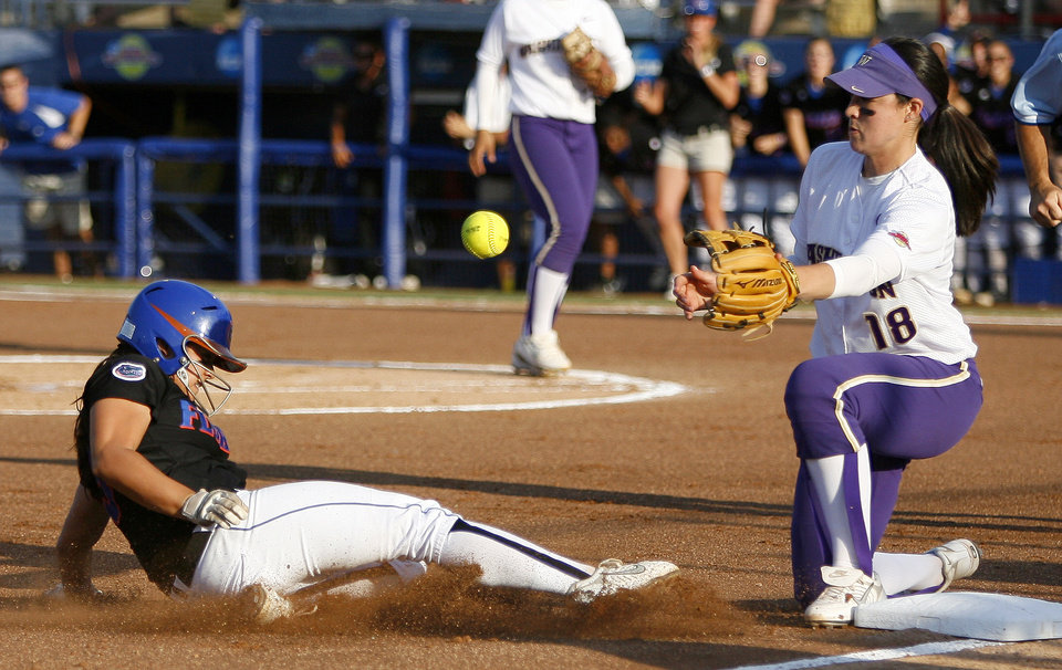Photo - COLLEGE SOFTBALL: University of Florida's Aja Paculba slides to third as Washington's Morgan Stuart waits for the ball in the first inning of the second softball game of the championship series between Washington and Florida in Women's College World Series at ASA Hall of Fame Stadium in Oklahoma City, Tuesday, June 2, 2009. Photo by Bryan Terry, The Oklahoman ORG XMIT: KOD