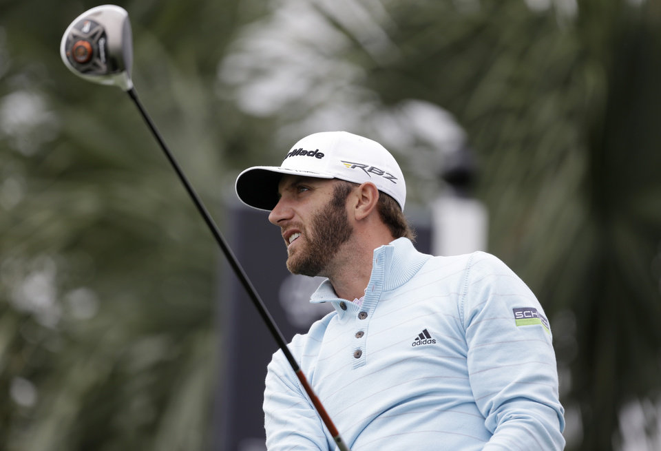 Photo - Dustin Johnson watches his shot after teeing off the 18th tee during the first round of the Honda Classic golf tournament, Thursday, Feb. 28, 2013 in Palm Beach Gardens, Fla. (AP Photo/Wilfredo Lee)