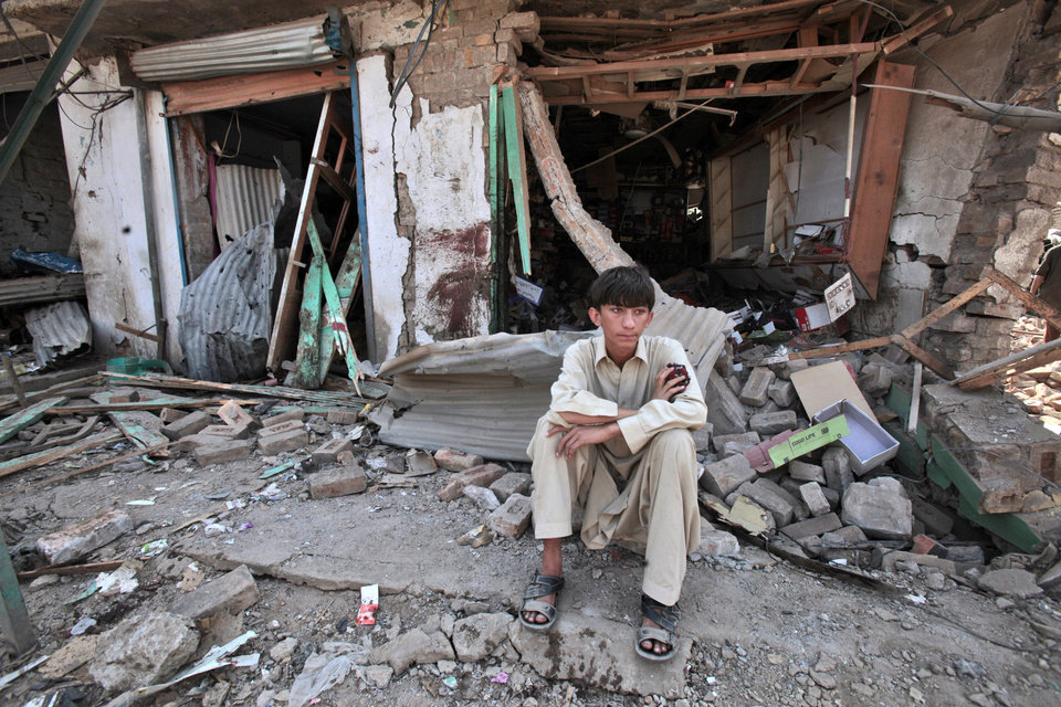 Photo -   A Pakistani youth sits amid the rubble of offices destroyed in a car bomb explosion in the Pakistani town of Darra Adam Khel in the troubled Khyber Pakhtunkhwa province bordering Afghanistan, Saturday, Oct. 13, 2012. A powerful car bomb went off outside the offices of pro-government tribal elders in northwestern Pakistan on Saturday, killing several people, police said. (AP Photo/Mohammad Sajjad)
