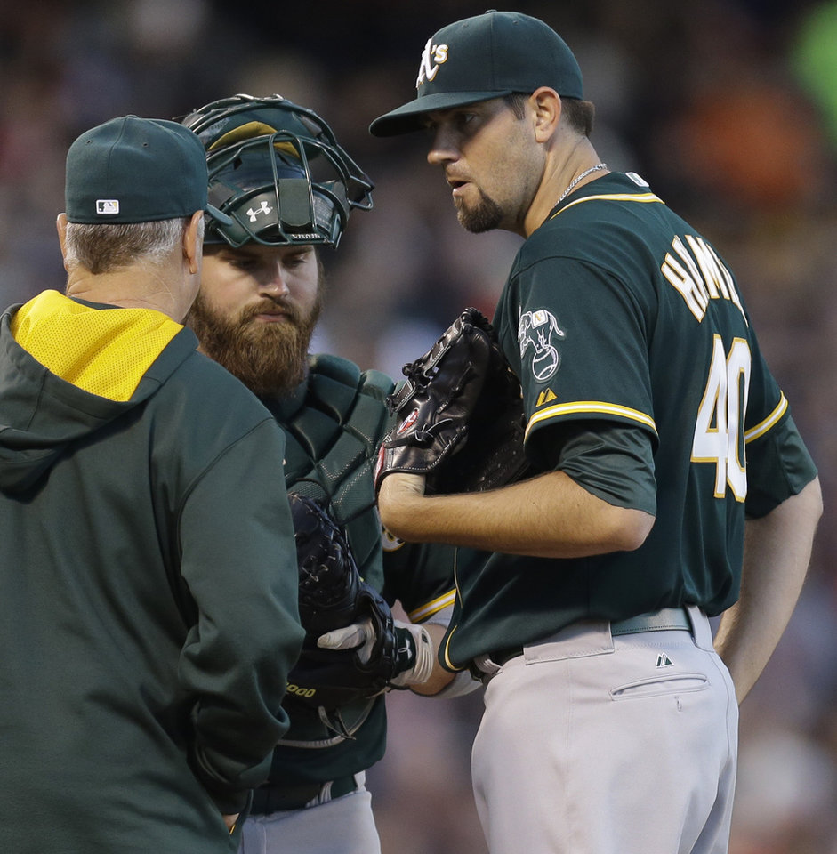 Photo - Oakland Athletics' Jason Hammel, right, speaks with pitching coach Curt Young and catcher Derek Norris in the third inning of a baseball game against the San Francisco Giants Wednesday, July 9, 2014, in San Francisco. (AP Photo/Ben Margot)